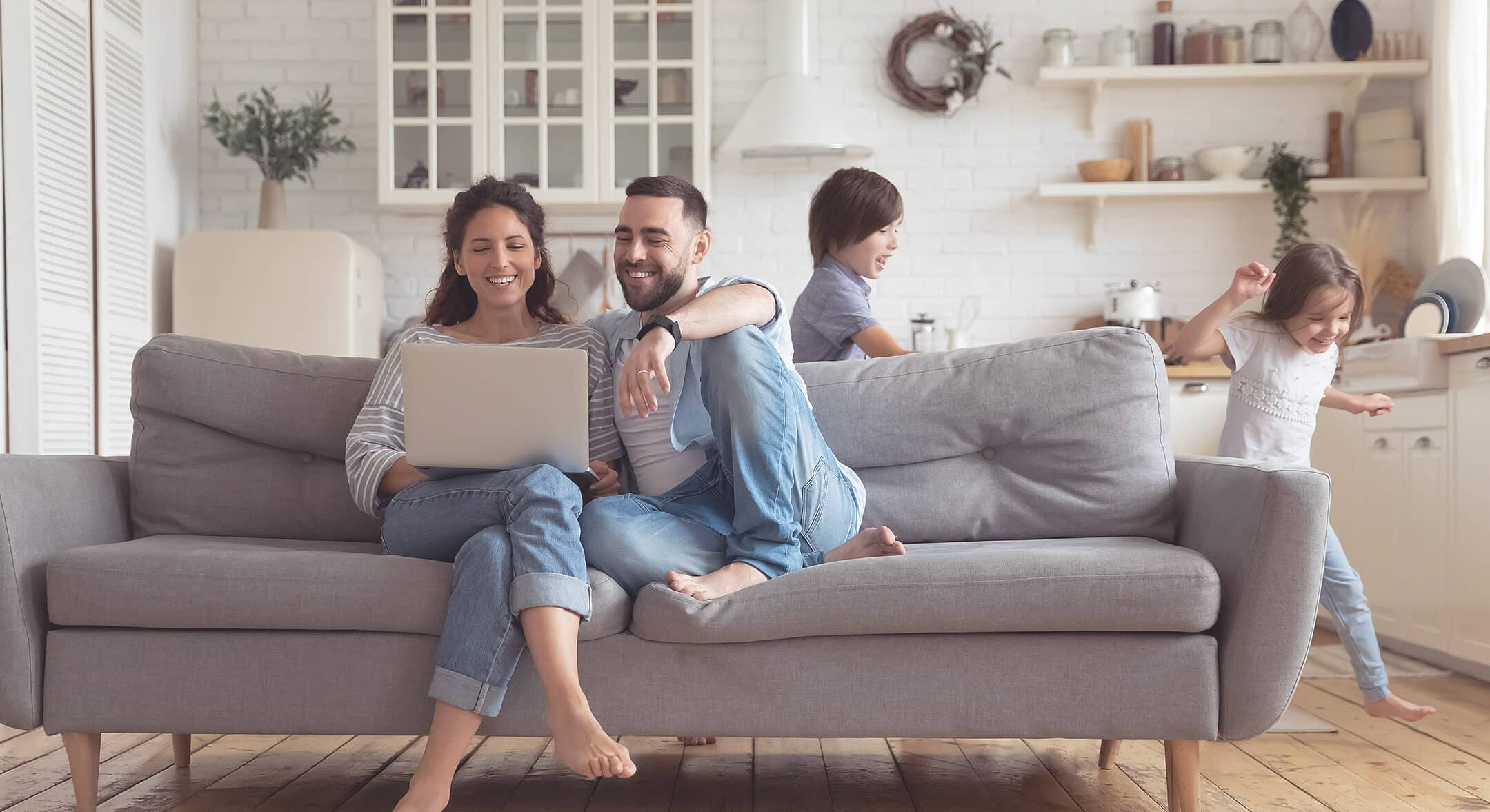 A family sitting in the living room, browsing a laptop about to apply for a mortgage.