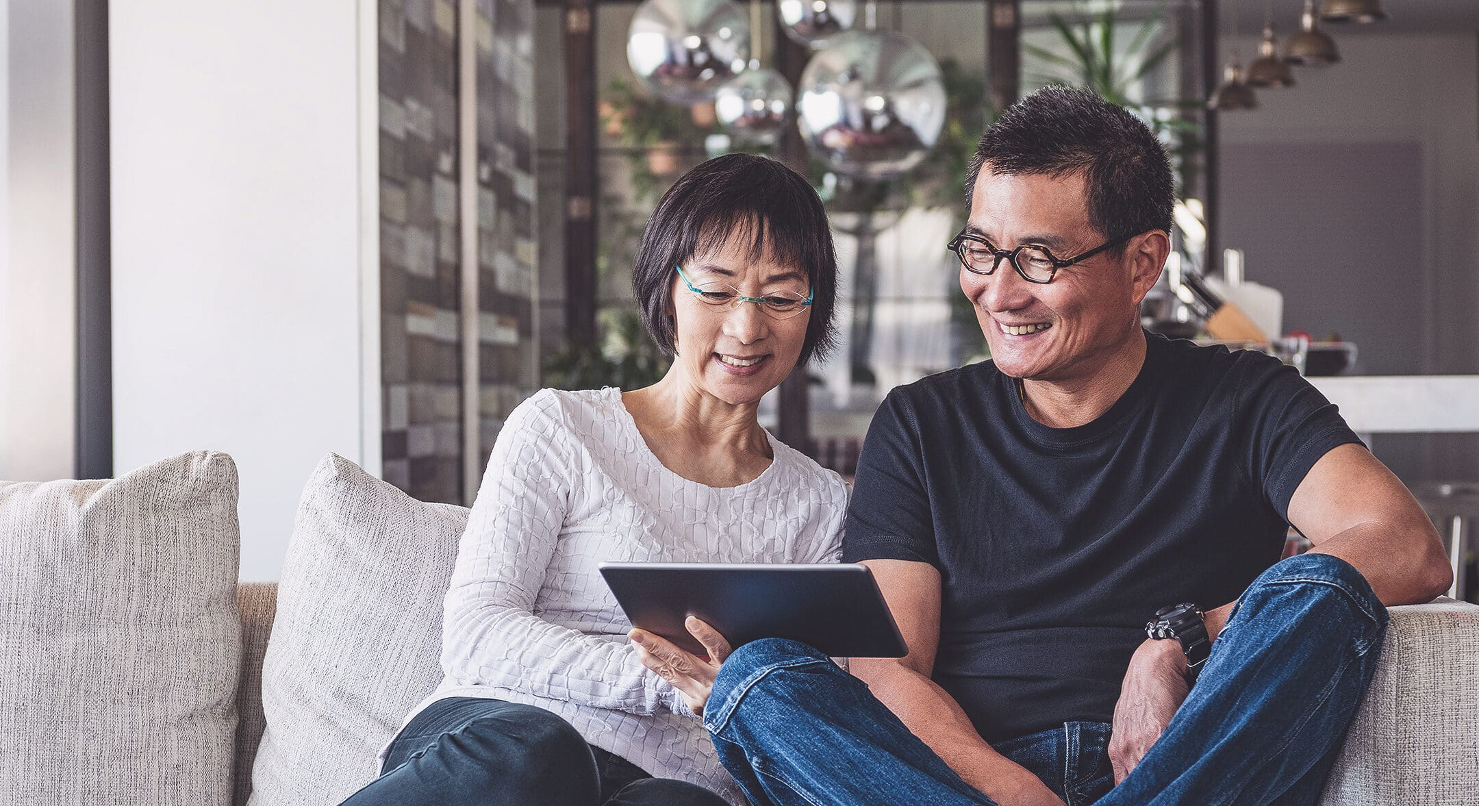 An older couple sitting on a couch browsing mortgage renewal options on a tablet.