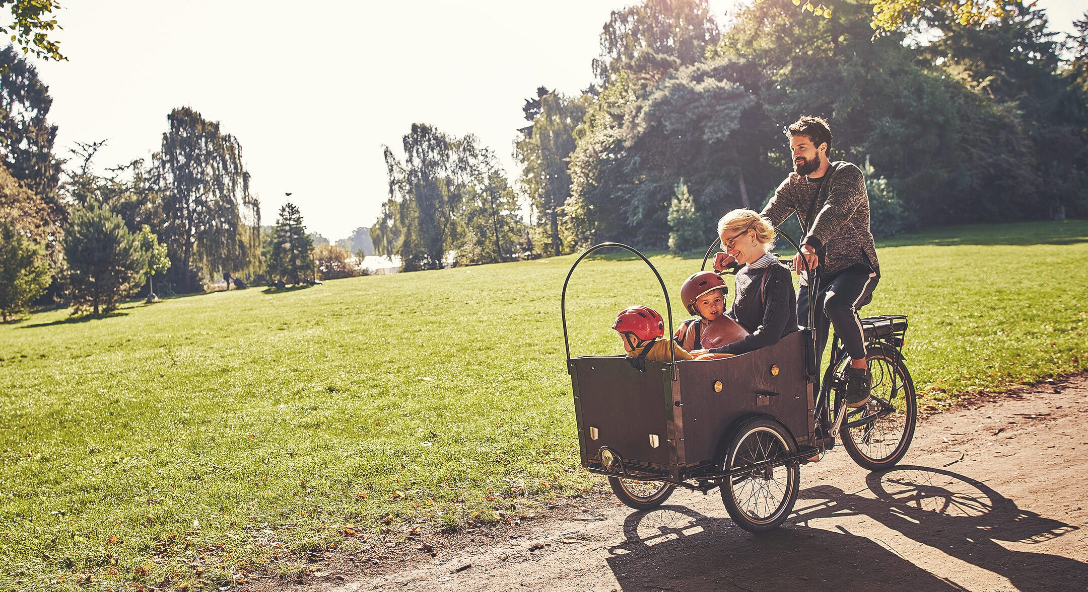 A young family riding a cargo bicycle through a park after purchasing their first home.